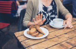 Young woman on gluten free diet is saying no thanks to toast in a cafe