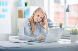 pale and tired woman working at a desk