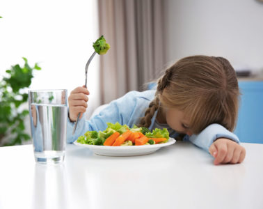 girl with head on table and fork of broccoli