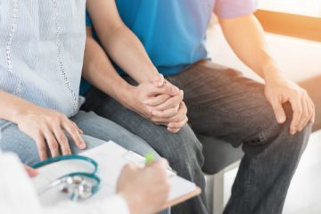 man and woman holding hands in medical setting
