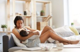 Young mum sitting on the couch breastfeeding